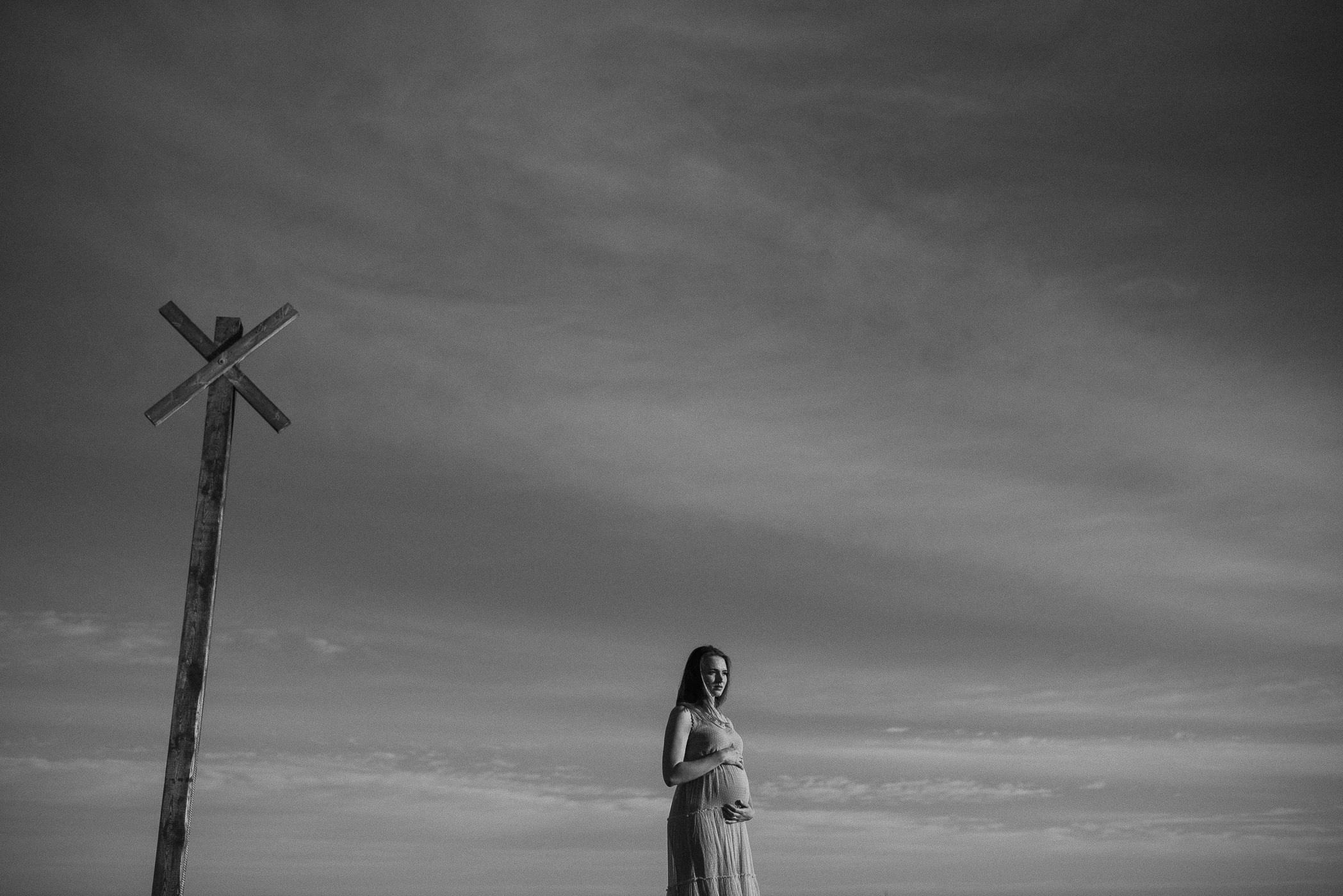 Kunstvolles Schwangerschaftsbild vor Himmel und Kreuz bei toller Sonnenuntergangsstimmung. Sonnenuntergang am Strand, Frau hält sich den dicken Bauch, Schwangere Frau, Wolken, klarer Himmel, schwarz, weiße Bilder einer Frau, fotografiert von Anne und Björn aus Lüneburg bei Hamburg