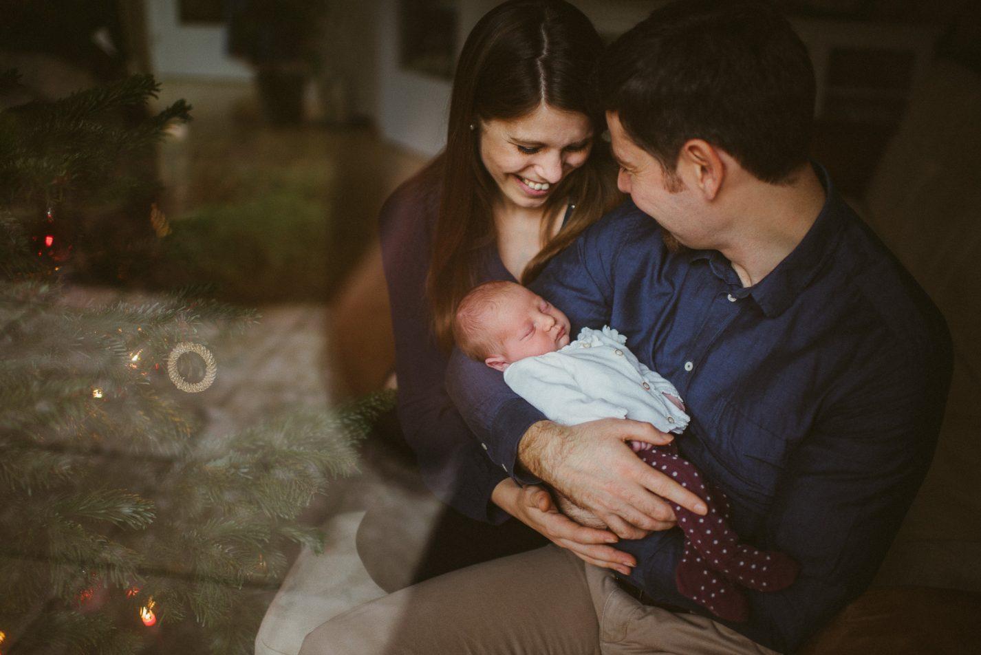 Eltern freuen sich über ihr neugeborenes Baby. Eltern sind verliebt. Weihnachten, Weihnachtsbaum, Zu hause, Babybilder in den eigenen vier wänden