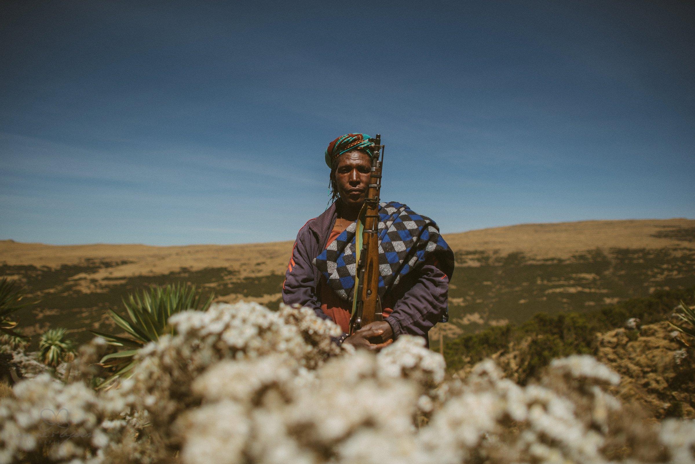 Mann mit Gewehr, Schutz, Guide, Africa, Blumen, Portrait, Reisefotograf